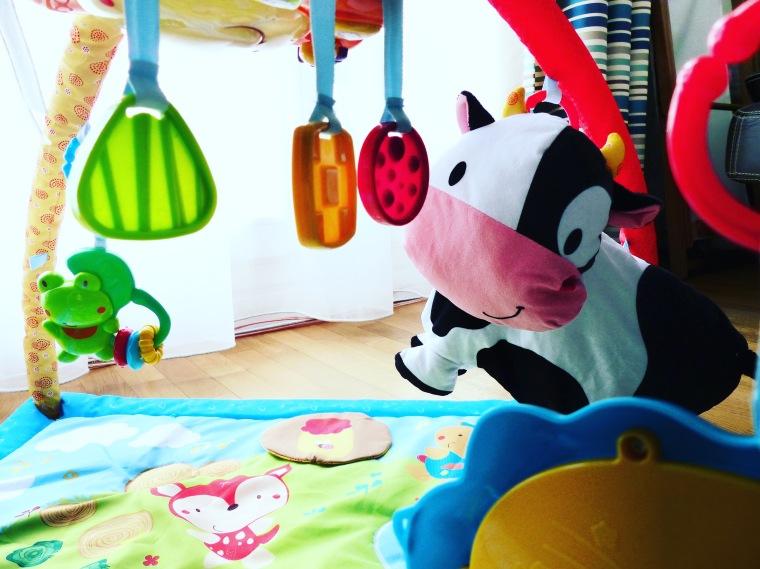 Paul commence à apprivoiser sa grosse vache suspendue et tous les petits animaux accrochés à l'arche du tapis